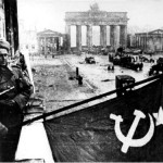 Soviet soldiers hosting the Soviet flag on the balcony of Hotel Adlon in Berlin after the fall of the city. Bundesarchiv, Bild 183-R77767 / CC-BY-SA